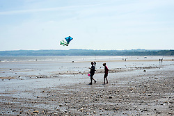 Holiday makers flying a childs kite  head out across the flat Beach during the May Bank Holiday. Filey, North Yorkshire<br />  <br /> 21 May 2013<br /> Image © Paul David Drabble<br /> www.pauldaviddrabble.co.uk