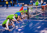 Australian Open tournament volunteers mop rainwater from under the center court net at Rod Laver Arena in Melbourne. A shower deluged the venue for a few minutes before the arena roof could be slowly closed.