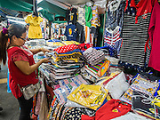 23 AUGUST 2014 - BANGKOK, THAILAND: A Thai woman sets up her clothing stand at a night sidewalk market on Sukhumvit Road near Soi 5 in the Nana section of Bangkok. The Thai military junta, formally called the National Council for Peace and Order (NCPO), has ordered street vendors off of the sidewalks in an effort to bring order to Bangkok's chaotic sidewalks. Vendors have complained that the new regulations are hurting them economically but largely complied with the military orders.       PHOTO BY JACK KURTZ