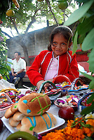 """MEXICO, Veracruz, Tantoyuca, Oct 27- Nov 4, 2009. A young girl smiles shyly behind her class altar at Tantoyuca's Roberto Medellin primary school. """"Xantolo,"""" the Nahuatl word for """"Santos,"""" or holy, marks a week-long period during which the whole Huasteca region of northern Veracruz state prepares for """"Dia de los Muertos,"""" the Day of the Dead. For children on the nights of October 31st and adults on November 1st, there is costumed dancing in the streets, and a carnival atmosphere, while Mexican families also honor the yearly return of the souls of their relatives at home and in the graveyards, with flower-bedecked altars and the foods their loved ones preferred in life. Photographs for HOY by Jay Dunn."""