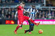 Liverpool's Defender Alberto Moreno  beats Newcastle United's Midfielder Moussa Sissoko  to the ball during the Barclays Premier League match between Newcastle United and Liverpool at St. James's Park, Newcastle, England on 6 December 2015. Photo by George Ledger.