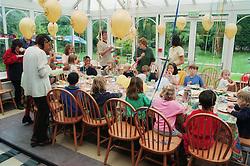 Children sitting around table at child's birthday party,