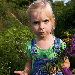 A young girl in a garden in Gloucester Massachusetts USA