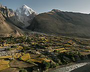 View over Mount Baba high above (6,513 meters, 21300 feet). Villages rely on subsistence agriculture that depends on water which is brought from the snout of the glaciers via an intricate water channel systems. The life of the Wakhi people, in the Wakhan corridor, amongst the Pamir mountains. Trekking with Paul Salopek.