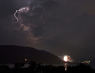 Newburgh, New York - Lightning illuminates the sky while fireworks explode alongthe Hudson River in a view looking south on July 4, 2012. ©Tom Bushey / The Image Works