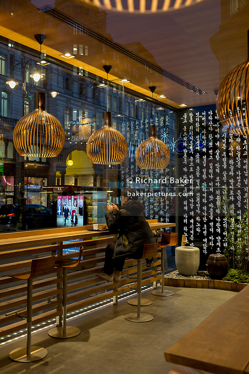 A young man in a 'Kimchee To Go' bar sits at a high table overlooking the Strand, on 12th December 2017, in London England.