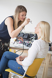 Woman being rouged from a make-up artist using airbrush