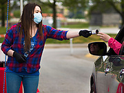 06 MAY 2020 - DES MOINES, IOWA: ANNA SERVEY, from Cedar Ridge Winery and Distillery practices social distancing while she hands a bottle of hand sanitizer to a motorist in a drive through at Principal Park, the stadium for the Iowa Cubs, the minor league baseball team affiliated with the Chicago Cubs. Two months after the start of the COVID-19 pandemic Iowa retailers still can't keep everyday items like hand sanitizer, toilet paper, and alcohol based cleaning supplies in stock. Many of the artisan distilleries in Iowa have started making and distributing free hand sanitizer.         PHOTO BY JACK KURTZ