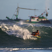 A local teenage body boarder in action as a fishing trawler sails past  during a big swell in the late afternoon sun at Arpoador Beach near Apoador Point, Rio de Janeiro,  Brazil. 18th August 2010. Photo Tim Clayton..