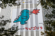 """Baby godzilla cartoon breaths red fire on building in Shinjuku ward, Tokyo, Japan. The character first appeared in Ishiro Honda's 1954 film Godzilla and became a worldwide pop culture icon, appearing in various media, including 32 films produced by Toho, three Hollywood films and numerous video games, novels, comic books and television shows. It is often dubbed """"the King of the Monsters"""", a phrase first used in """"Godzilla, King of the Monsters!"""", the Americanized version of the original film."""