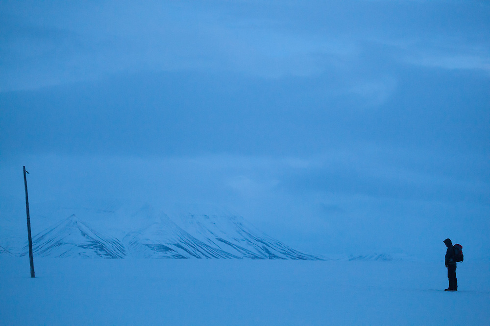A man stands alone facing an abandoned utility pole on Sverdruphamaren, Svalbard.