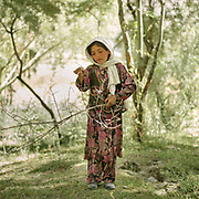 Girl picking wood in planted forest. The traditional life of the Wakhi people, in the Wakhan corridor, amongst the Pamir mountains.
