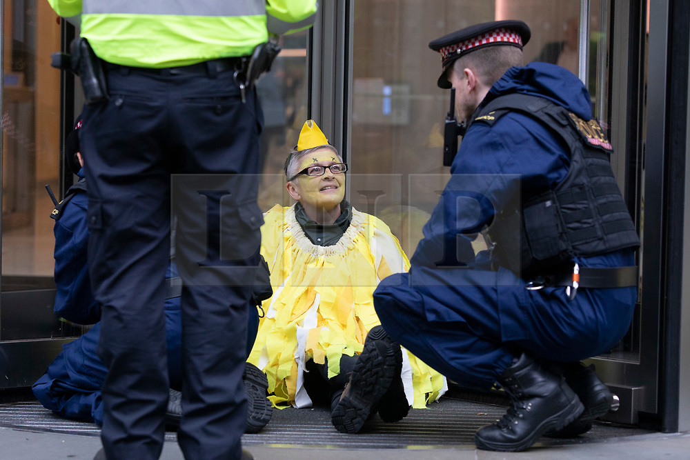 © Licensed to London News Pictures. 14/10/2019. London, UK. An Extinction Rebellion protester dressed as a canary remains glued on to the Walkie Talkie building . Protesters are today targeting the financial district.  Photo credit: George Cracknell Wright/LNP