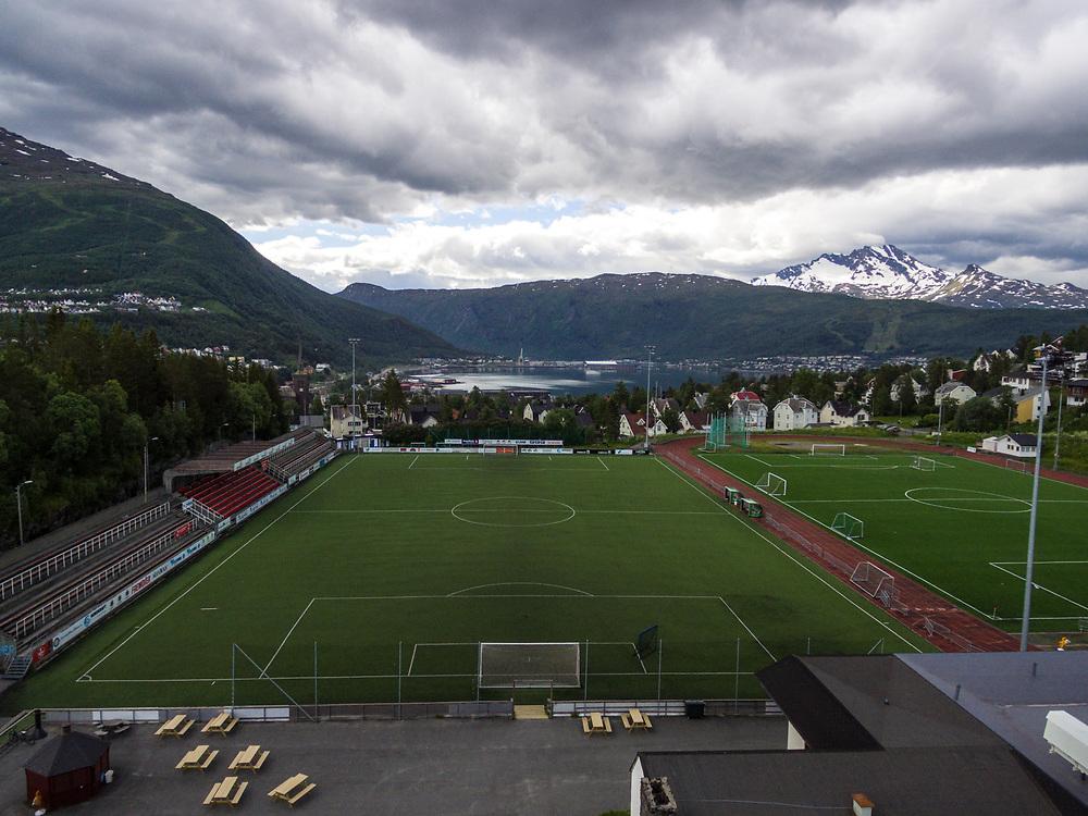 Oversiktsbilde som viser hovedbanen på Narvik stadion. Tribuneanlegget til venstre, og byen og dronninga i bakgrunnen.