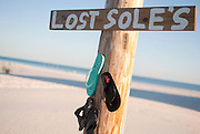 """A humorous sign stating, """"lost soles,"""" hangs above individual flip-flops on the beach in Fort Morgan, Alabama."""
