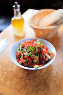An attractive fresh salad of diced tomatoes and cucumbers, together with a wicker basket of warm pita bread, on a restaurant table. WATERMARKS WILL NOT APPEAR ON PRINTS OR LICENSED IMAGES.