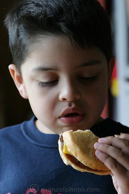 (MODEL RELEASED IMAGE). At home in San Antonio, Texas, 5-year-old Brian Fernandez polishes off a cheeseburger from the fast-food chain, Whataburger. (Supporting image from the project Hungry Planet: What the World Eats.)