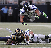 Football - NFL- Seattle Seahawks at St. Louis Rams.Seattle Seahawks linebacker Malcolm Smith (53) leaps horizontally over St. Louis Rams wide receiver Austin Pettis (18) who has the ball, and Seattle Seahawks free safety Earl Thomas (29, right) who was in on the tackle that brought Pettis down in the second quarter at the Edward Jones Dome in St. Louis.  The Rams defeated the Seahawks, 19-13.