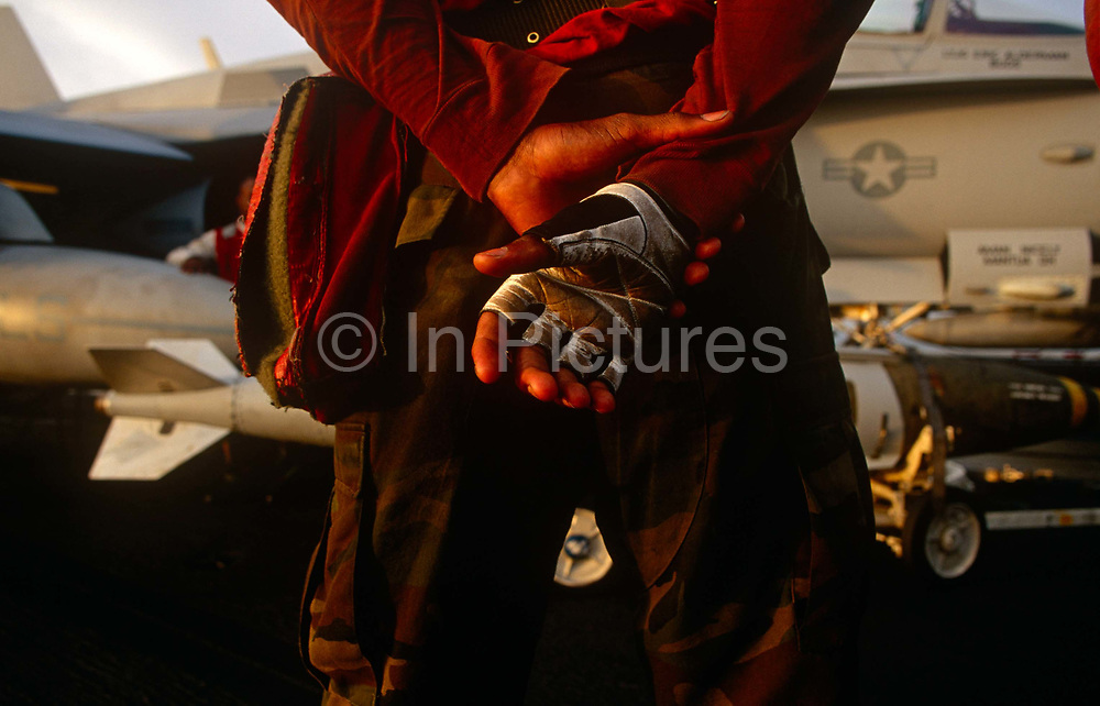 A red shirted ordnance man prepares to fit smart bombs to an F/A-18 fighter jet on deck of USS Harry S Truman. Launched on 7 September 1996 and costing US$4.5 billion, the Truman (CVN-75) is the eighth Nimitz-class supercarrier of the United States Navy, named after the 33rd President of the United States, Harry S. Truman. The Truman is the largest of the US Navy's fleet of new generation carriers, a 97,000 ton floating city with a crew of 5,137, 650 are women.