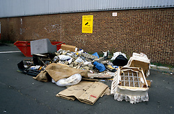 Fly tipped rubbish in front of sign dumping of rubbish prohibitied CCTV in operation; UK