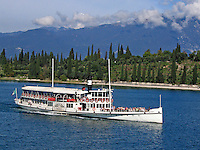 Lake Garda, Italy, ferry, ferry boat, paddle steamer, lake, blue sky, trees, forest, shoreline, coastline, mountains, blue sky, white clouds, 200609180047.<br /> <br /> Copyright Image from Victor Patterson, Belfast, UK<br /> <br /> t: +44 28 9066 1296 (from Rep of Ireland 048 9066 1296)<br /> m: +44 7802 353836<br /> e: victorpattersonbelfast@gmail.com<br /> <br /> www.images4media.com<br /> <br /> Please see my full Terms and Conditions of Use at https://www.images4media.com/p/terms-conditions - it is IMPORTANT that you familiarise yourself with them.<br /> <br /> Images used online incur an additional cost. This cost should be agreed in writing in advance. Online images must be visibly watermarked i.e. © Victor Patterson or that of the named photographer within the body of the image. The original metadata must not be deleted from images used online.<br /> <br /> This image is only available for the use of the download recipient i.e. television station, newspaper, magazine, book publisher, etc, and must not be passed on to a third party. It is also downloaded on condition that each and every usage is notified within 7 days to victorpattersonbelfast@gmail.com.<br /> <br /> The right of Victor Patterson (or the named photographer) to be identified as the author is asserted in accordance with The Copyright Designs And Patents Act (1988). All moral rights are asserted.