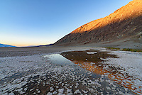 The golden colors of sunset are reflected in the salt pool at Badwater Basin. At 282 feet below sea level, this is the lowest point in North America.