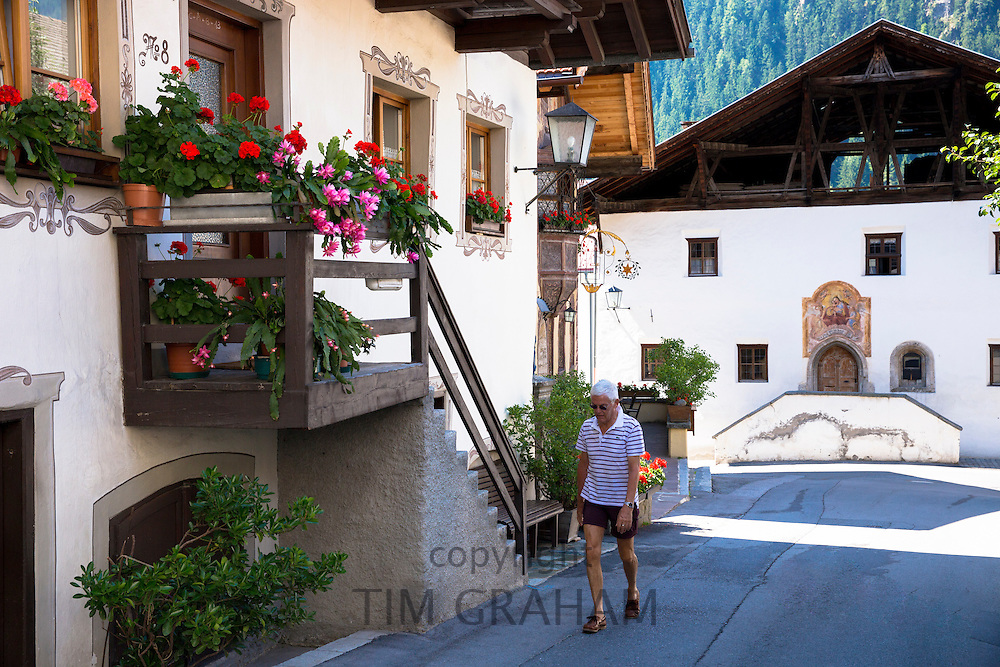 Man walks along Kirchweg in the old part of the town of Oetz in the Tyrol, Austria