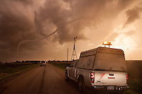 A tornado ropes out at sunset near Russel, Kansas, May 25, 2012.  The vehicle in the foreground is a research vehicle operated by Tim Marshall and working in conjunction with Project ROTATE.