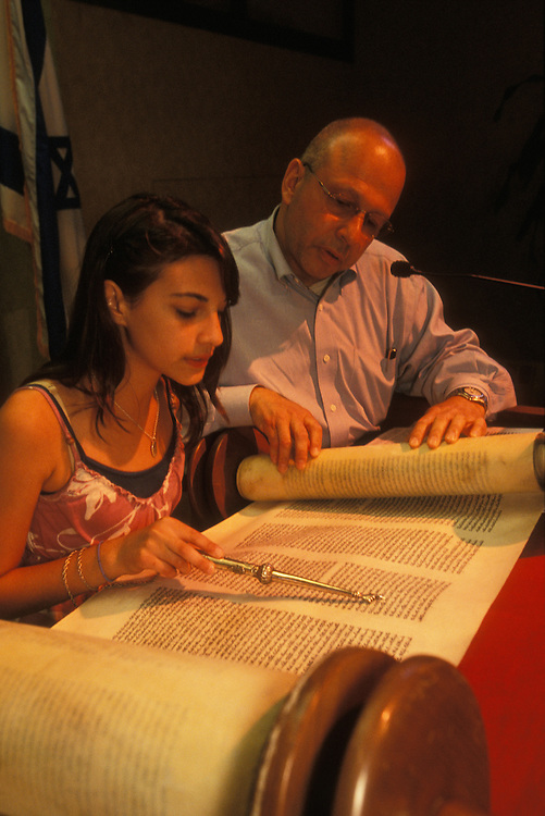 Guided by her rabbi a Jewish girl practices reading from the Torah, the five books of Moses, in preparation for her bat mitzvah, her coming of age ceremony, in Fair Lawn, New Jersey, USA. Jewish tradition dictates that a girl comes of age at twelve, though in Reform and Conservative Jewish congregations they usually become bat mitzvahs at thirteen, the same age as boys.