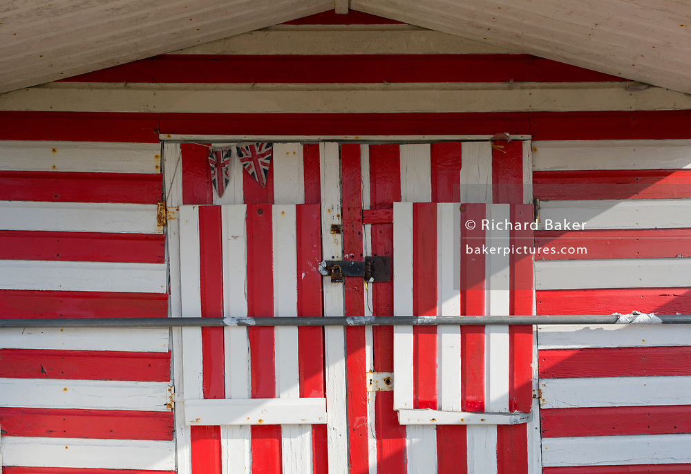 The detail of two sad bunting Union Jacks on the exterior of a red and white striped wooden beach hut, on 31st March 2019, in Whitstable, Kent, England.