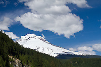 Mt Hood under a sunny blue sky with fluffy white clouds