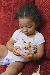 Neglected toddler sitting on sofa wearing dirty clothes and holding a box of matches,