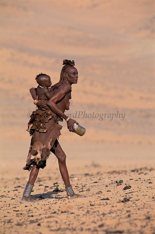 Himba woman carring a baby on her back. Kaokoland, Namibia