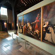 A triptych painting and nun's habit on display at Old St. John's Hospital in Bruges, Belgium. Old St. John's Hospital is one of Europe's oldest surviving hospital buildings that dates to the 11th century. It originally treated sick pilgrims and travelers. A monastery and convent was later added. It is now a museum.