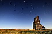 Star trails and moonlit grain elevator in ghost town<br /> Bents<br /> Saskatchewan<br /> Canada