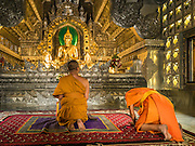 "03 APRIL 2016 - CHIANG MAI, THAILAND: A Buddhist monks pray in the ordination hall of Wat Sri Suphan. Wat Sri Suphan is also known as the ""Silver Temple"" because of its silver ubosot, or ordination hall. The temple is more than 500 years old but the silver ordination hall was recently remodeled. The ordination hall is covered in silver and the interior is completely done in silver and gold. It's traditionally served as the main temple for the silversmiths of Chiang Mai, whose community is around the temple.     PHOTO BY JACK KURTZ"