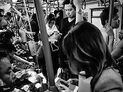 08 FEBRUARY 2017 - BANGKOK, THAILAND: Commuters riding the BTS (Bangkok Skytrain) check their smart phones.         PHOTO BY JACK KURTZ