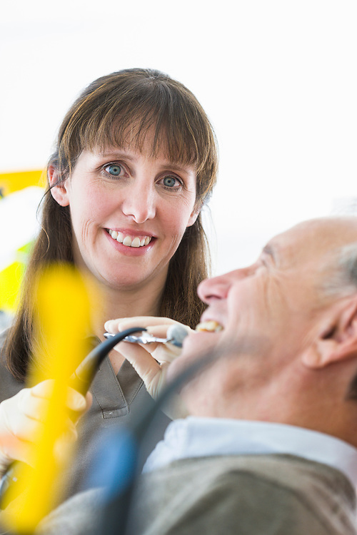 a female dentist expaminating the teeth on an old man