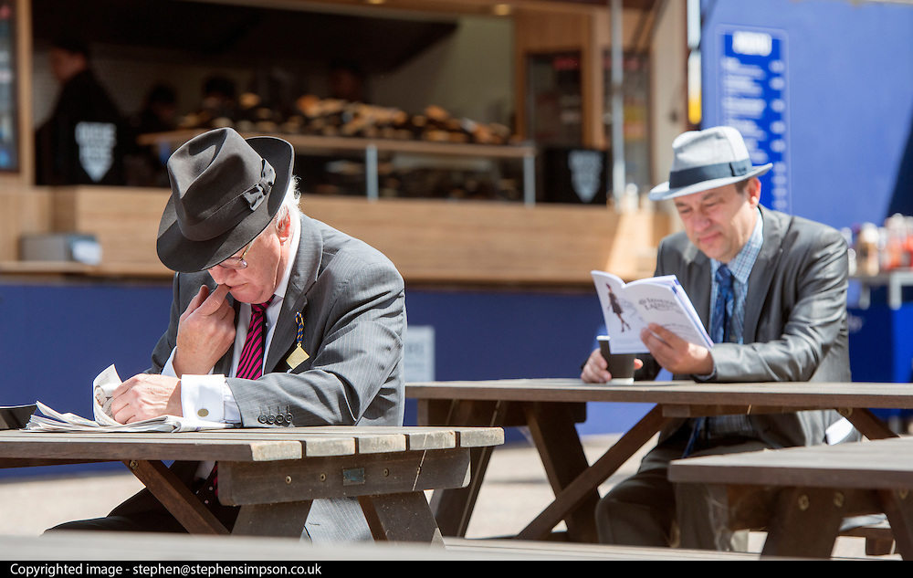 TODAY PICTURE © Licensed to London News Pictures. 06/06/2014. Epsom, UK. Men read their Race Cards.  Ladies Day today 6th June 2014 at Epsom 2014 Investic Derby Festival in Surrey. Traditionally, elegant, fashionable racegoers gather for a classic day's racing at Epsom Racecourse, Surrey. Photo credit : Stephen Simpson/LNP
