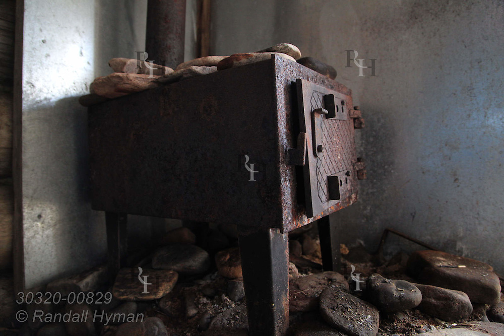 Wood stove sits inside rustic sauna at trapper's hut in remote fjord called Austfjorden in Svalbard, Norway.