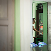A server works at the popular restaurant Huyen Anh Restaurant, Hue, Vietnam. The restaurant specializes in bún thịt nướng, cold rice noodle dish topped with fresh herbs, vegetables, grilled pork and peanuts and served with a side of a sweet, vinegary, fish sauce-based dipping sauce infused with garlic and peppers.