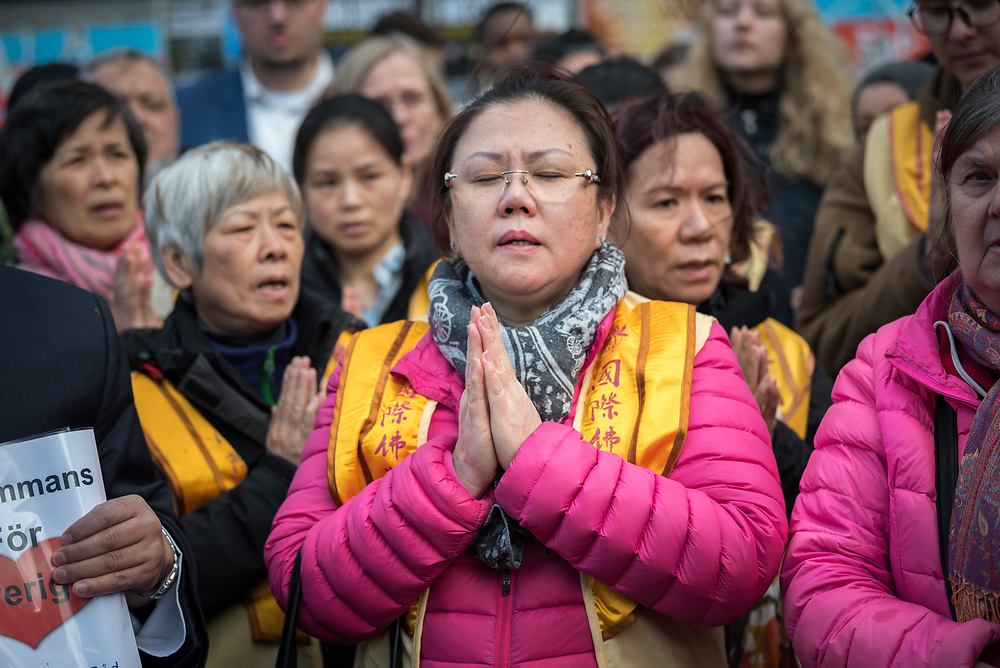"""10 April 2017, Stockholm, Sweden: Three days after a lorry was driven into a store in central Stockholm, killing at least four people and injuring many more, an interreligious service was held at Sergels torg in central Stockholm, to commemorate the victims of violence, and to pray together, for a future of compassion and peace together. The event was attended by representatives of a range of religions present in Stockholm and Sweden as a whole. Here, Buddhist participants sharing a """"Mantra of Love""""."""