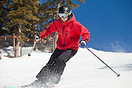 Woman skiers skiing on a sunny hard packed day.