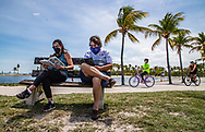Barbara and Gary Keisberg take time to read their books while visiting Matheson Hammock Park on Saturday, May 2, 2020 as Miami-Dade County opens parks and marinas this week.