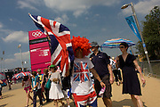 An eccentric Brit sports fan marches towards the Velodrome in the Olympic Park during the London 2012 Olympics. In the background is one of the giant pillar signs showing landmark directions. Wearing a red wig and Union Jack t-shirt and shorts, he walks along aone of the main avenues along with thousands of other spectators. This land was transformed to become a 2.5 Sq Km sporting complex, once industrial businesses and now the venue of eight venues including the main arena, Aquatics Centre and Velodrome plus the athletes' Olympic Village. After the Olympics, the park is to be known as Queen Elizabeth Olympic Park.