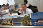 Employees in a central London office work dilligently alongside the reminders of vacations that colleagues and friends have taken. Picture postcard souvenirs have been lined up as a display of the perfect holiday when they have returned to work to put their shoulders to the grindstone. It is a scene of wishful thinking, of 'wish you were here!' and of looking forward to the next break from the toil of their careers so by showing the idyllic locations of their dreams with these visual reminders, can they imagine the beauty of these places: Tenby in south Wales, the Lake District in northern England and a country hall set in, perhaps, the Scottish  hills. An out of focus worker stares intensely into his PC, perhaps thinking of escapism and a life outside these four walls.