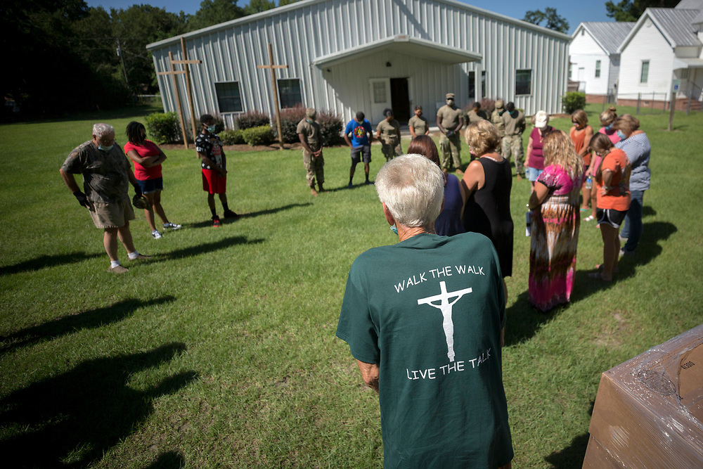 SUMMERTOWN, GA - JULY 14, 2020: Summertown Food Pantry volunteer Paul Pierre leads a group in prayer, blessing the food they are about to give to the 116 people lined up in their cars. (AJC Photo/Stephen B. Morton)