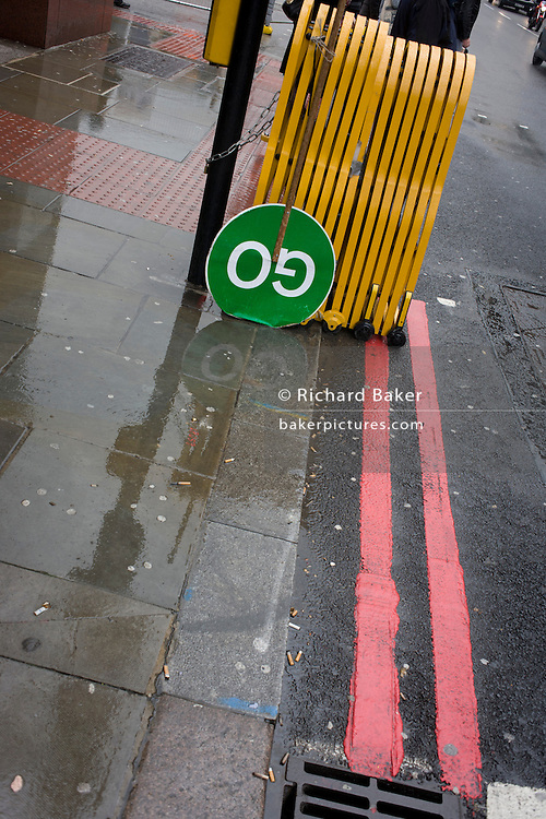 An upside down GO construction traffic sign in a busy London rush-hour street.