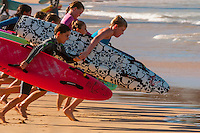 Young surfers sprinting as a group to enter the water on the surfboards, Manly Beach, Sydney, New South Wales, Australia
