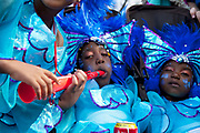 Kids dressed up in costumes at Notting Hill Carnival in West London. The Notting Hill Carnival is an annual event which since 1964 has taken place each August, over two days (the August bank holiday Monday and the day beforehand). It is led by members of the West Indian / Caribbrean community, particularly the Trinidadian and Tobagonian British population, many of whom have lived in the area since the 1950s. The carnival has attracted up to 2 million people in the past, making it the second largest street festival in the world. The celebration centres around a parade of floats, dancers and sound systems.